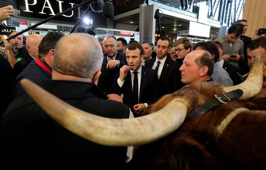 "French President Emmanuel Macron, center, tastes some food while listening exhibitors as he visits the 56th International Agriculture Fair at the Porte de Versailles exhibition center in Paris, France, Saturday, Feb. 23, 2019. Macron pledged to protect European farming standards and culinary traditions threatened by aggressive foreign trade practices that see food as a ""product like any other."""