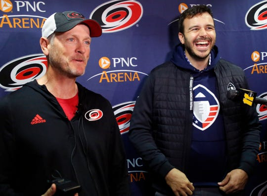 Tom Dundon, left, majority owner of the Carolina Hurricanes and Charlie Ebersol, co-founder and CEO of the Alliance of American Football talk to the media about Dundon's $250 million investment in the AAF before the start of a Hurricanes-Rangers game.