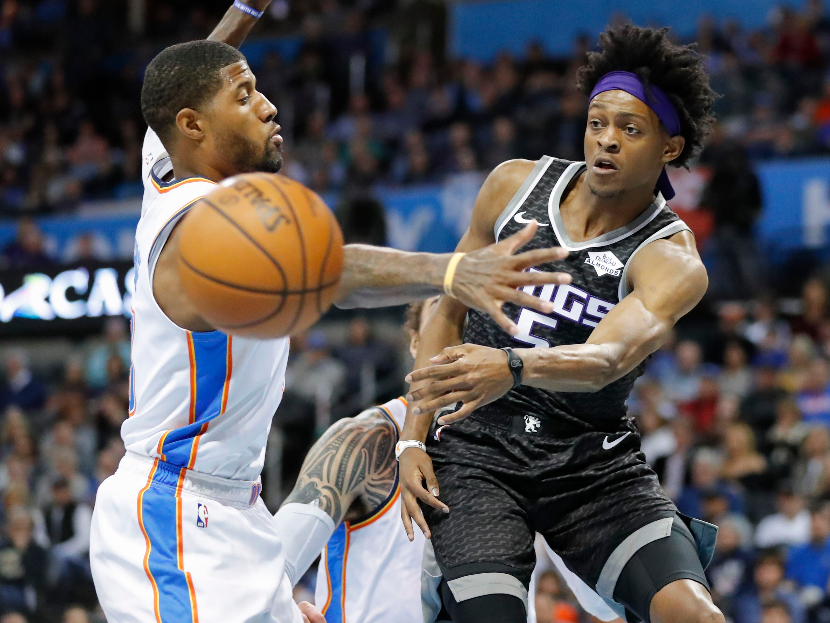 Feb. 23: Kings guard De'Aaron Fox (5) passes around Thunder defender Paul George (13) during the first half in Oklahoma City.