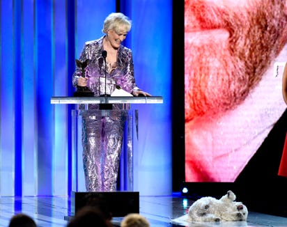 """Glenn Close accepts her Spirit Award for best female lead in """"The Wife,"""" as her dog, Pip, shows his support."""