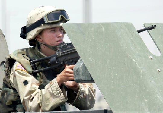 A female soldier mans a machine gun on a vehicle during clashes in the northern Iraqi city of Mosul in 2003. A federal judge in Texas has ruled that now that combat roles are available to women, a male-only draft is unconstitutional.