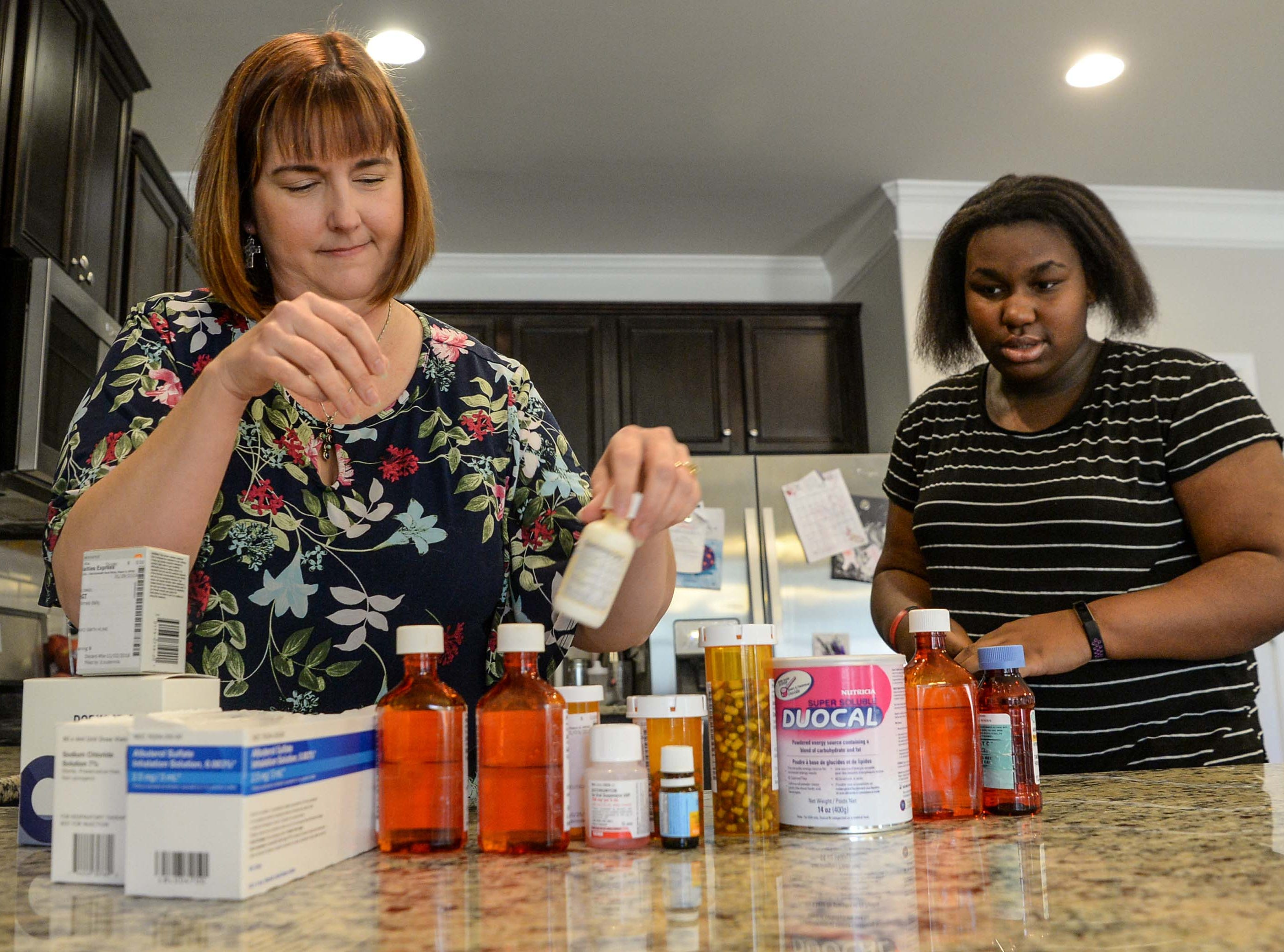 Ali Bragdon, left, of Anderson, CEO of Oasis of Hope foster care organization in Anderson, looks over medicines for two toddler foster children with daughter Erica Bragdon. Bragdon, one of the 39 children the couple has at some time cared for as foster parents, was adopted into the family.