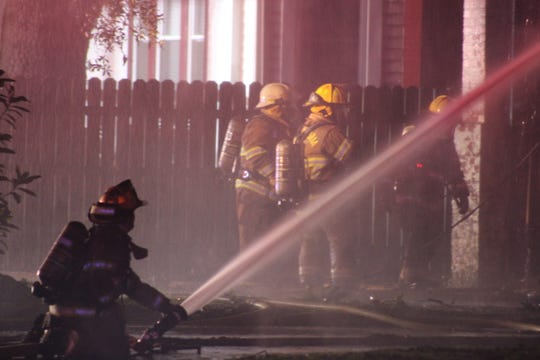 Alexandria Fire Department firefighters work at the scene of a two-alarm blaze on Polk Street late Sunday night. The cause of the fire remains under investigation.