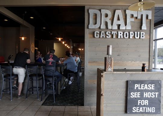 In this 2017 archive photo, Draft Gastropub staffers sit at the bar and go over menu items during training for the restaurant's reopening in Grand Chute. It had previously been located in Appleton.