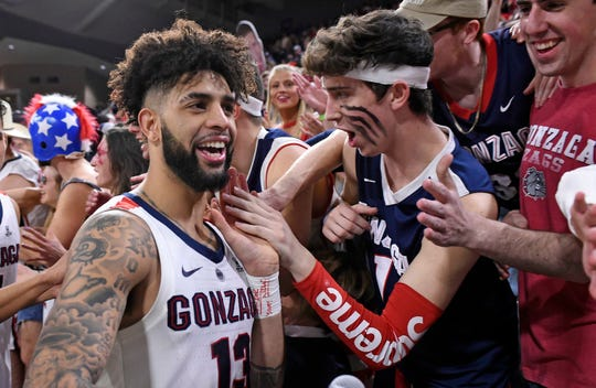 Gonzaga Bulldogs guard Josh Perkins (13) celebrates with the student section after a basketball game against the Brigham Young Cougars at McCarthey Athletic Center. The Bulldogs won 102-68.