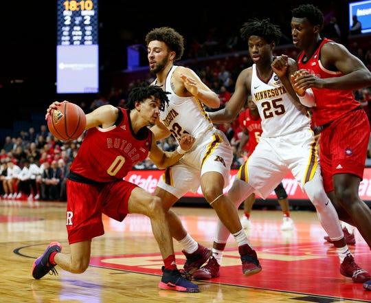 Rutgers Scarlet Knights guard Geo Baker (0) drives to the basket against Minnesota Golden Gophers guard Gabe Kalscheur (22) and center Daniel Oturu (25)