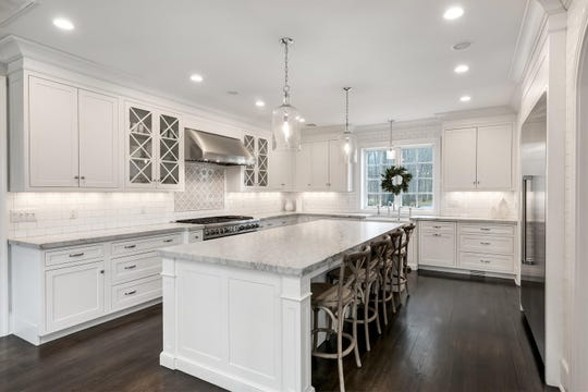 Designer kitchen features a large center island and custom cabinetry.