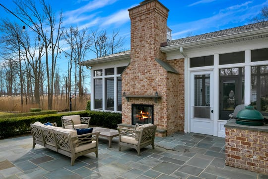 The backyard features a a dual sided fire place and blue stone patio