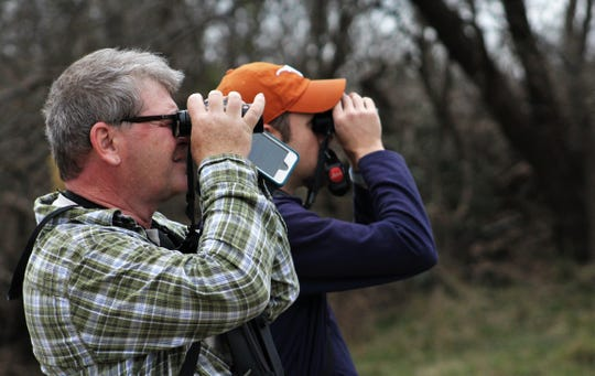 Do you see anything? Do you? David Sarkozi, left, and Jay Packer, double up on a look for birds in northeast Abilene in early February.