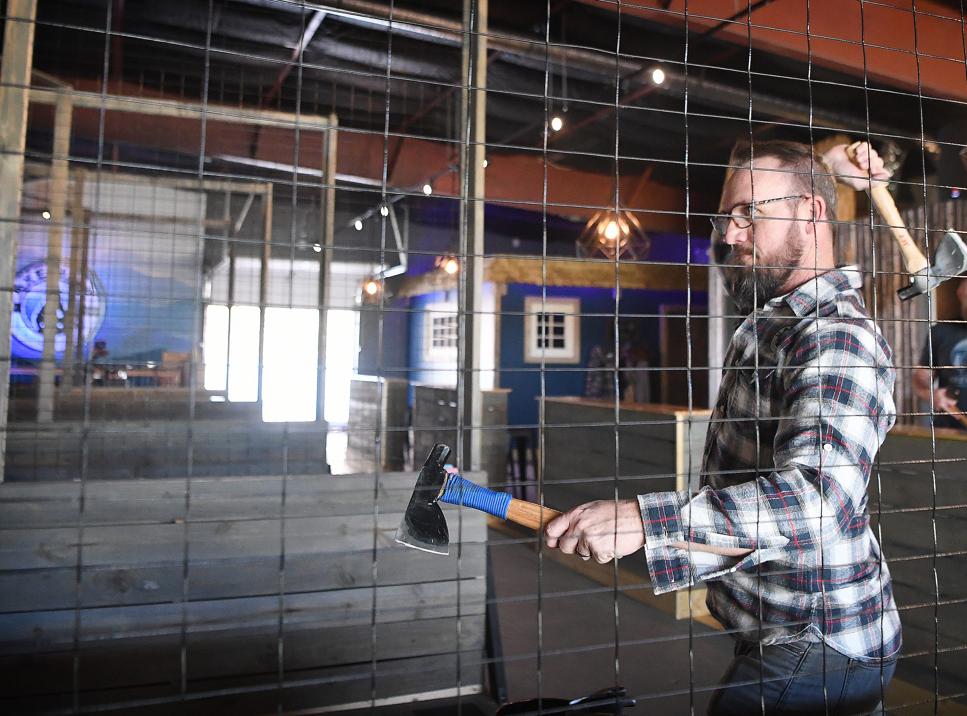 Axeville co-owner Ryan McClenny shows off his ax throwing skills at Axeville Throwing Club, Asheville's first ax throwing facility, which is planning to open to the public in March.  The club plans to be open Thursday and Friday evenings and most of the day on weekends.