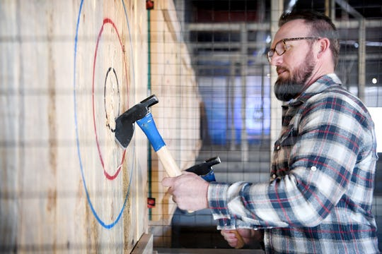 Axeville co-owner Ryan McClenny pulls his axes out of the target as he shows off his ax throwing skills at Axeville Throwing Club, Asheville's first ax throwing facility, which is planning to open to the public in March. The club will have coaches on hand to teach first-timers how to properly throw an ax.