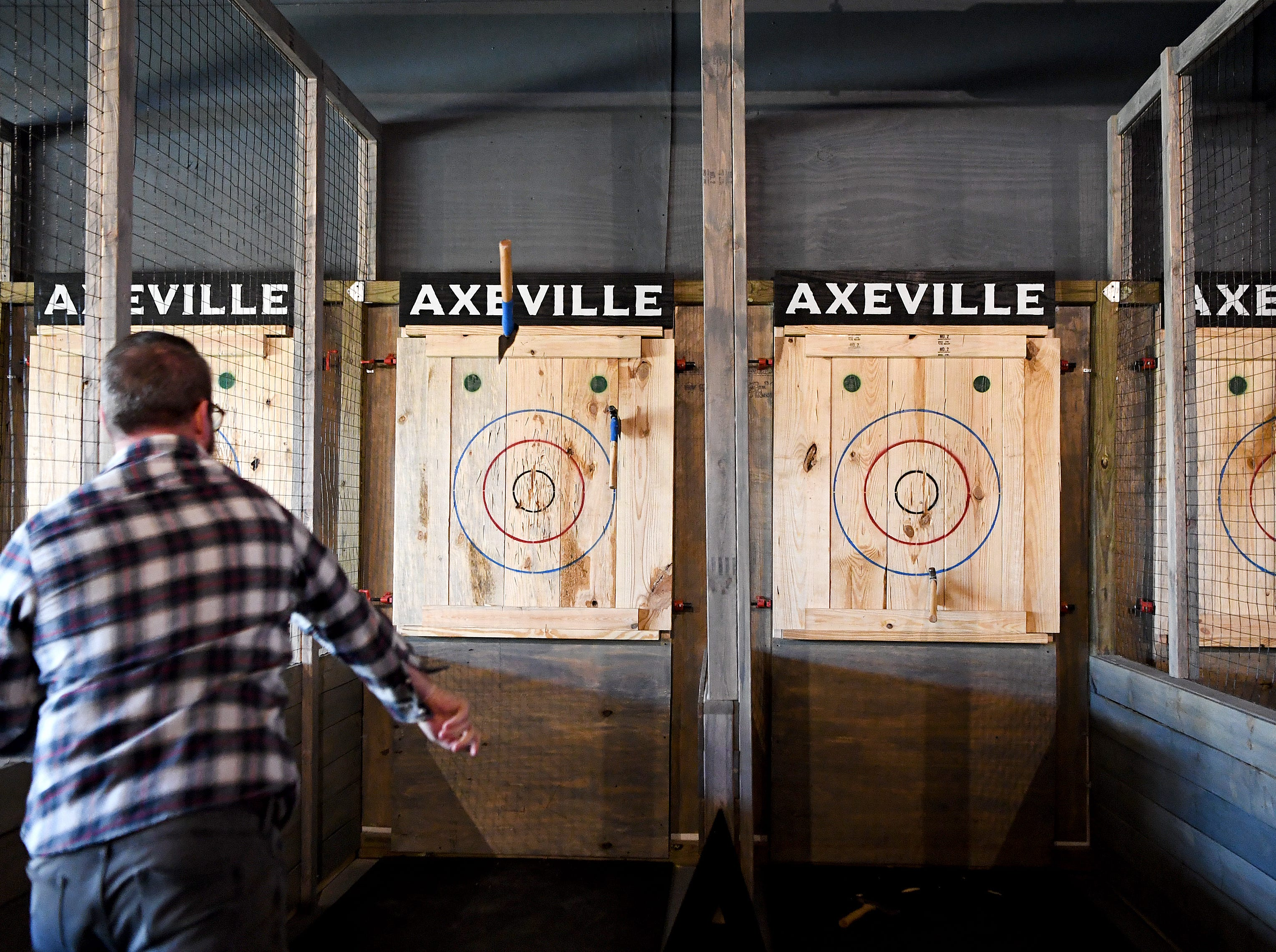 Axeville co-owner Ryan McClenny shows off his ax throwing skills at Axeville Throwing Club, Asheville's first ax throwing facility, which is planning to open to the public in March. The club will have coaches on hand to teach first-timers how to properly throw an ax.