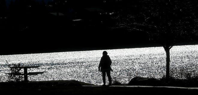 A walker is silhouetted against the glimmering water at Lions Park in Bremerton on a sunny Monday, February 25, 2019.