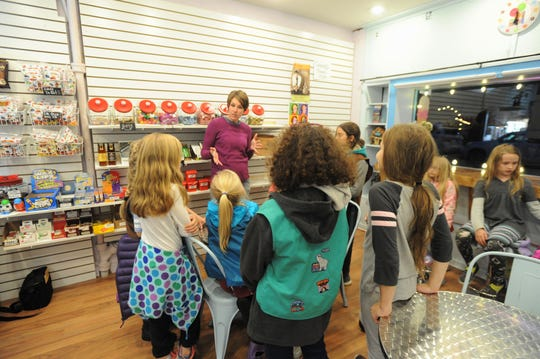 Ashley Garrison speaks to Girl Scout Troop 02498 in The Hop Ice Cream on Cherry Street in Black Mountain.
