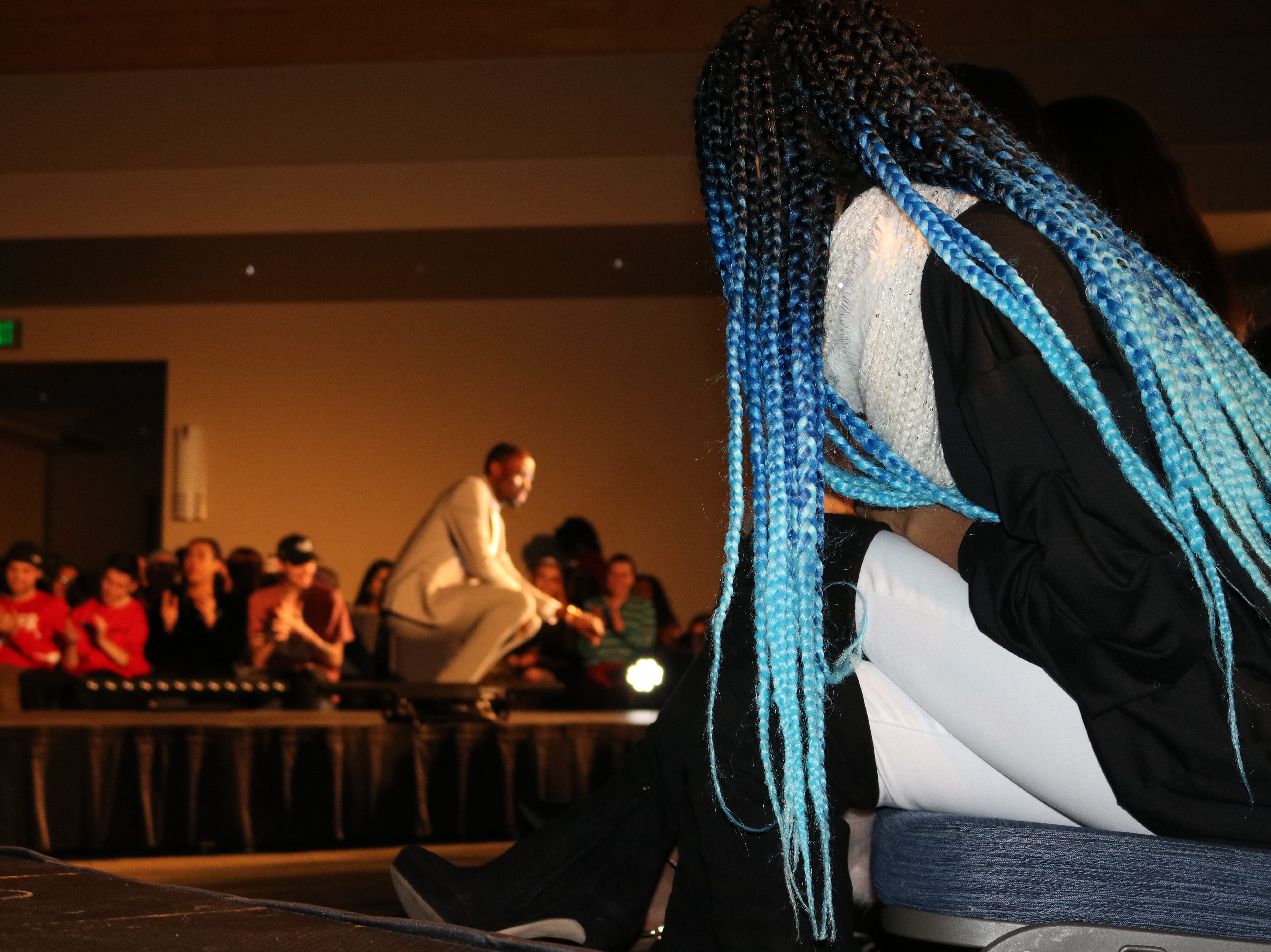 """There were lewks on and off the catwalk on Saturday, Feb. 23, 2019, at UVM's 2019 fashion show, """"Paint it Black."""" An audience member with blue ombre braids leans forward reacting to the charm of host Young Prince, seen in the background interacting with the crowd."""