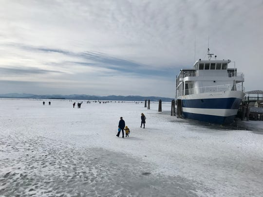 People walk on ice past the Spirit of Ethan Allen cruise boat docked by the Burlington Community Boathouse toward the breakwater in Burlington Bay on Saturday, Feb. 23, 2019. Much of Lake Champlain is frozen over after a stretch of cold days this winter.