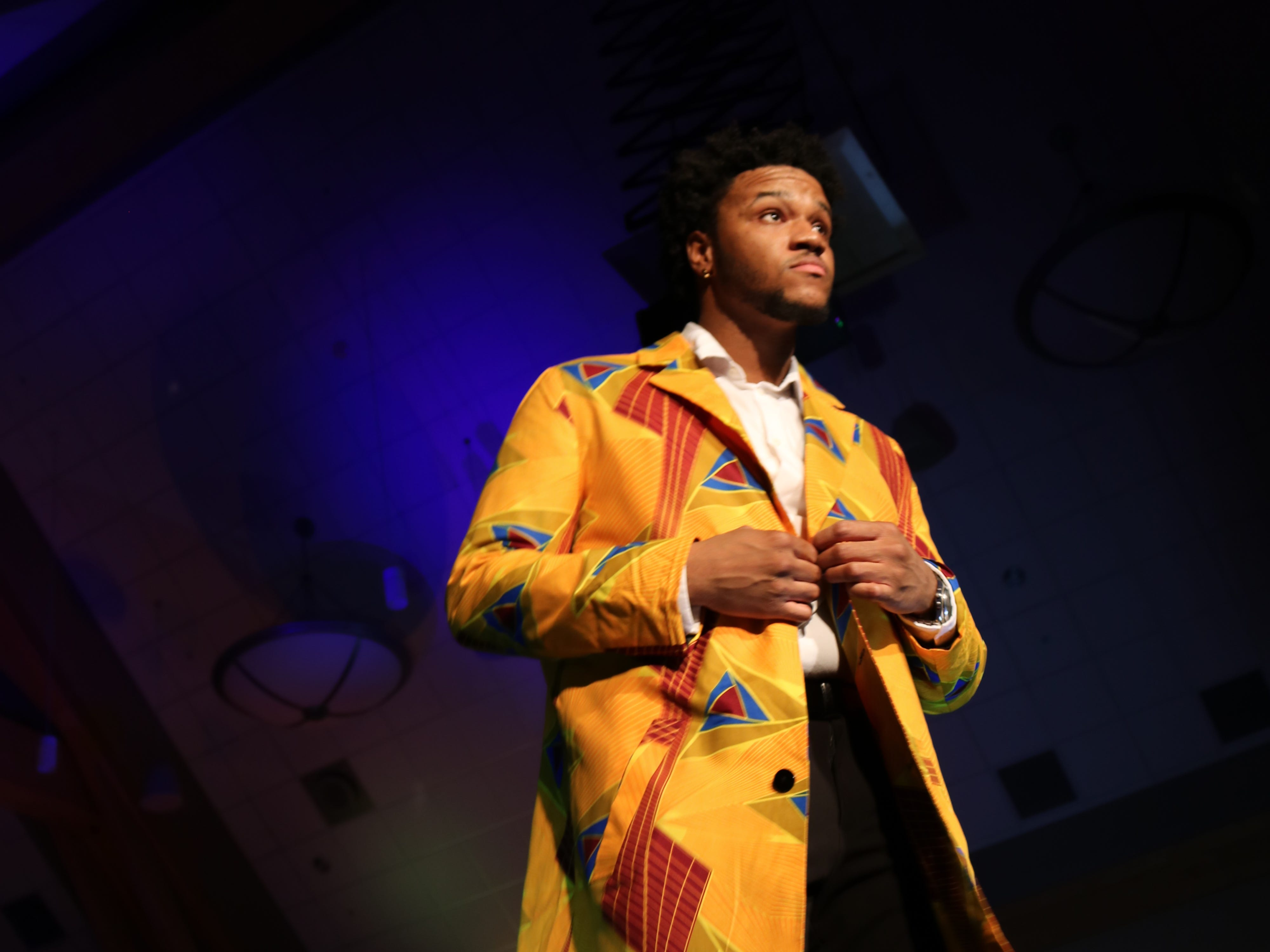 """UVM student shows off a vibrant yellow jacket as the crowd shouts praise at 2019 fashion show, """"Paint it Black,"""" on Saturday, Feb. 23, 2019, at the Davis Center."""