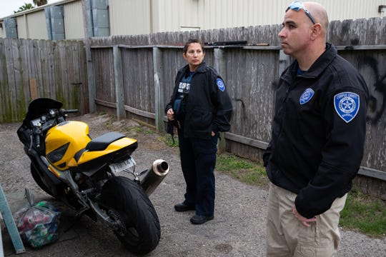 Corpus Christi City Marshal's Robert Rodriguez and Amanda Guerra wait for a person with an outstanding warrant to walk out of their home in Flour Bluff during the City's warrant roundup on Monday, Feb. 25, 2019.