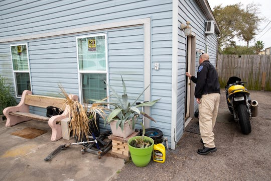 Corpus Christi City Marshal's Robert Rodriguez knocks next to an open door at a home Flour Bluff as they look for someone during the City's warrant roundup on Monday, Feb. 25, 2019.
