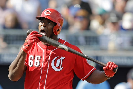 Cincinnati Reds' Yasiel Puig licks his bat during the third inning of a spring training baseball game against the Seattle Mariners, Monday, Feb. 25, 2019, in Peoria, Ariz.