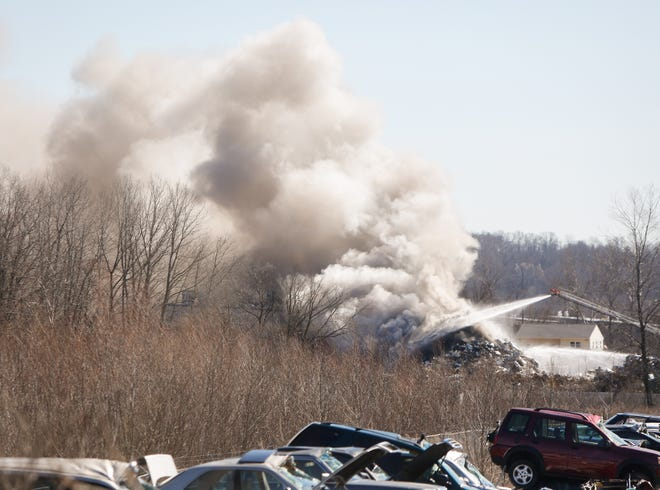 Firefighters work to extinguish a blaze at a Kellogg Avenue recycling center Monday.
