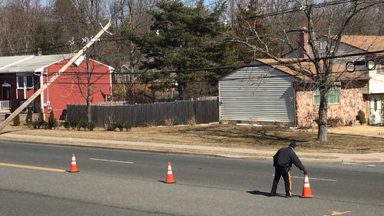 Leaning poles on power lines are a common sight in Central Jersey after hours of gale-force winds. Here a police officer places traffic cones on Ryders Lane in East Brunswick.