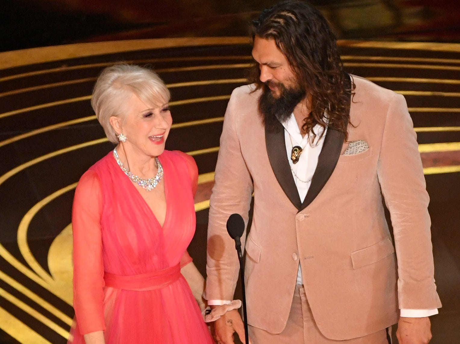 Helen Mirren and Jason Momoa speak on stage during the 91st Annual Academy Awards at Dolby Theatre on February 24, 2019 in Hollywood, California.