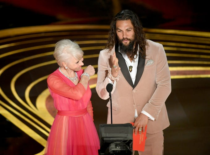 Helen Mirren and Jason Momoa speak onstage during the 91st Annual Academy Awards at Dolby Theatre on February 24, 2019 in Hollywood, California.