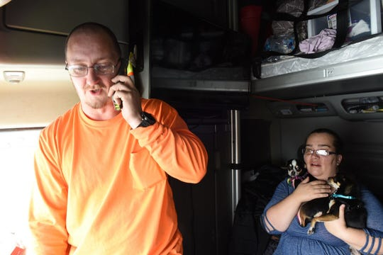 Jason Fincher, 37, talks to a family member on the phone as his wife, Christina Mull, 39, holds their dogs Bella and Buddy on Monday, Feb. 25, 2019, inside Fincher's semi truck. The San Antonio couple has been stranded in central Iowa since Saturday evening as they wait for northbound Interstate 35 to re-open so they can deliver a shipment to St. Paul, Minnesota.