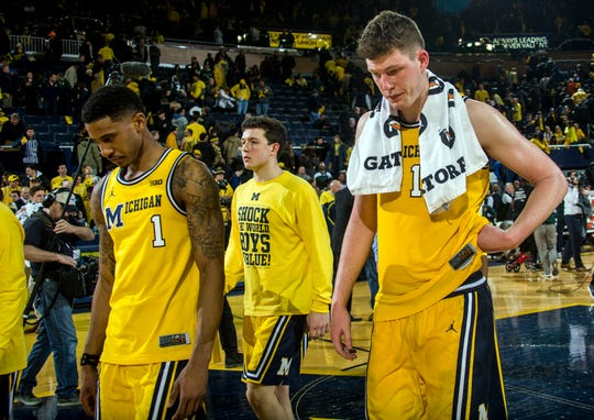 Michigan guard Charles Matthews (1) and center Jon Teske, right, walk off the court after a 77-70 loss to Michigan State at Crisler Center in Ann Arbor, Sunday, Feb. 24, 2019.