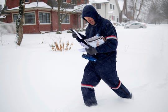 United States Postal Service letter carrier Keith Caniff sorts mail on his route in East Grand Rapids.