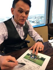 """Macomb County Executive Mark Hackel shows a copy of a $600 check that he says count Prosecutor Eric Smith wrote from what Hackel called """"a secret account"""" for four tickets to a golf fundraiser in August. Smith, two friends and Smith's brother Bob — who is chairman of the county Board of Commissioners — were players. Hackel on Monday called for the state attorney general to investigate Smith."""