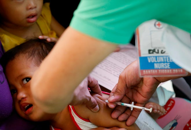 FILE - In this Feb. 16, 2019, file photo, Philippine National Red Cross and Health Department volunteers conduct house-to-house measles vaccination to children at an informal settlers community in Manila, Philippines. The Philippine health secretary says 136 mostly children have died of measles and 8,400 others have been downed by the contagious viral disease in an outbreak partly blamed on a vaccination scare in recent years.