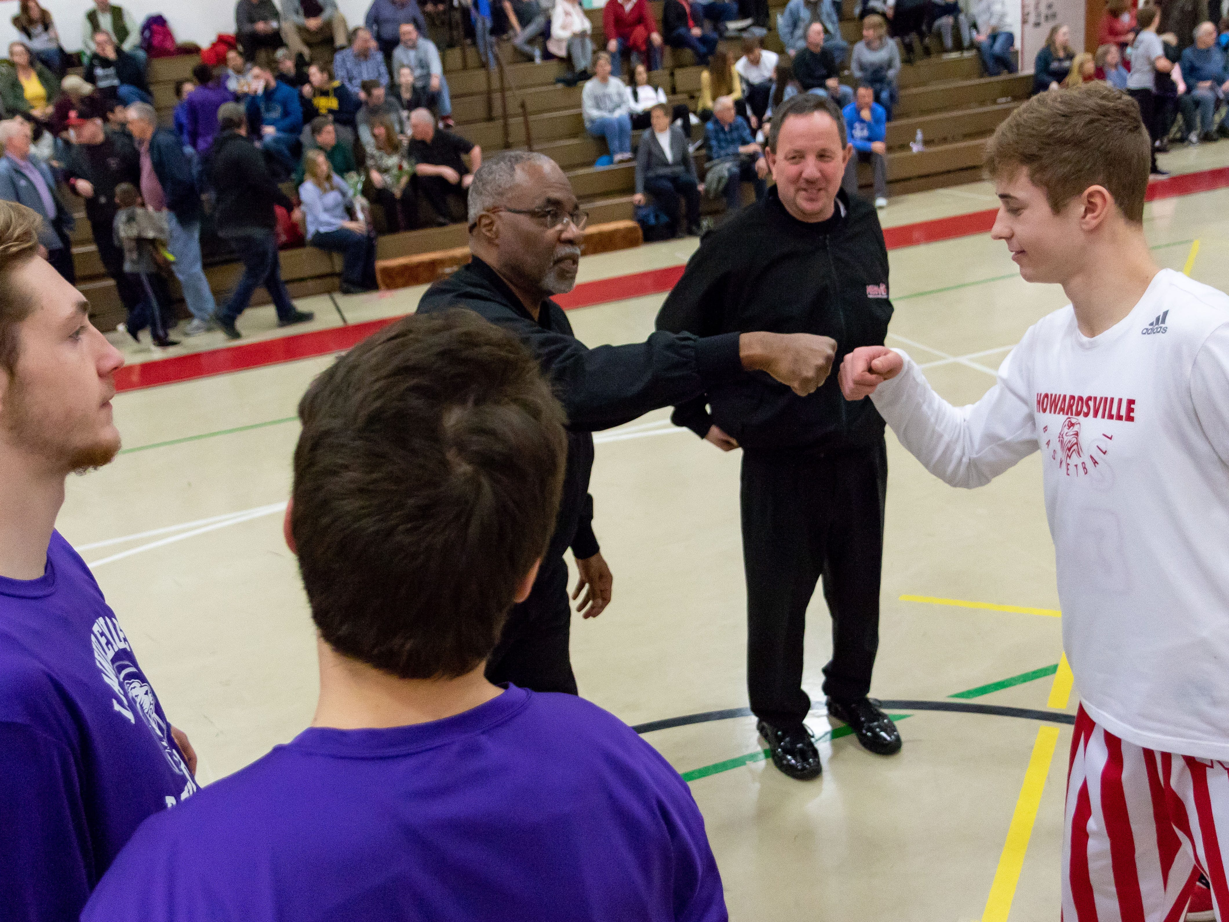 Dylan Jergens of Marcellus Howardsville Christian greets the game officials and captains for Lawrence before Saturday's game.
