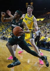 Michigan State's Cassius Winston drives around Michigan's Jon Teske to the hoop in the first half.