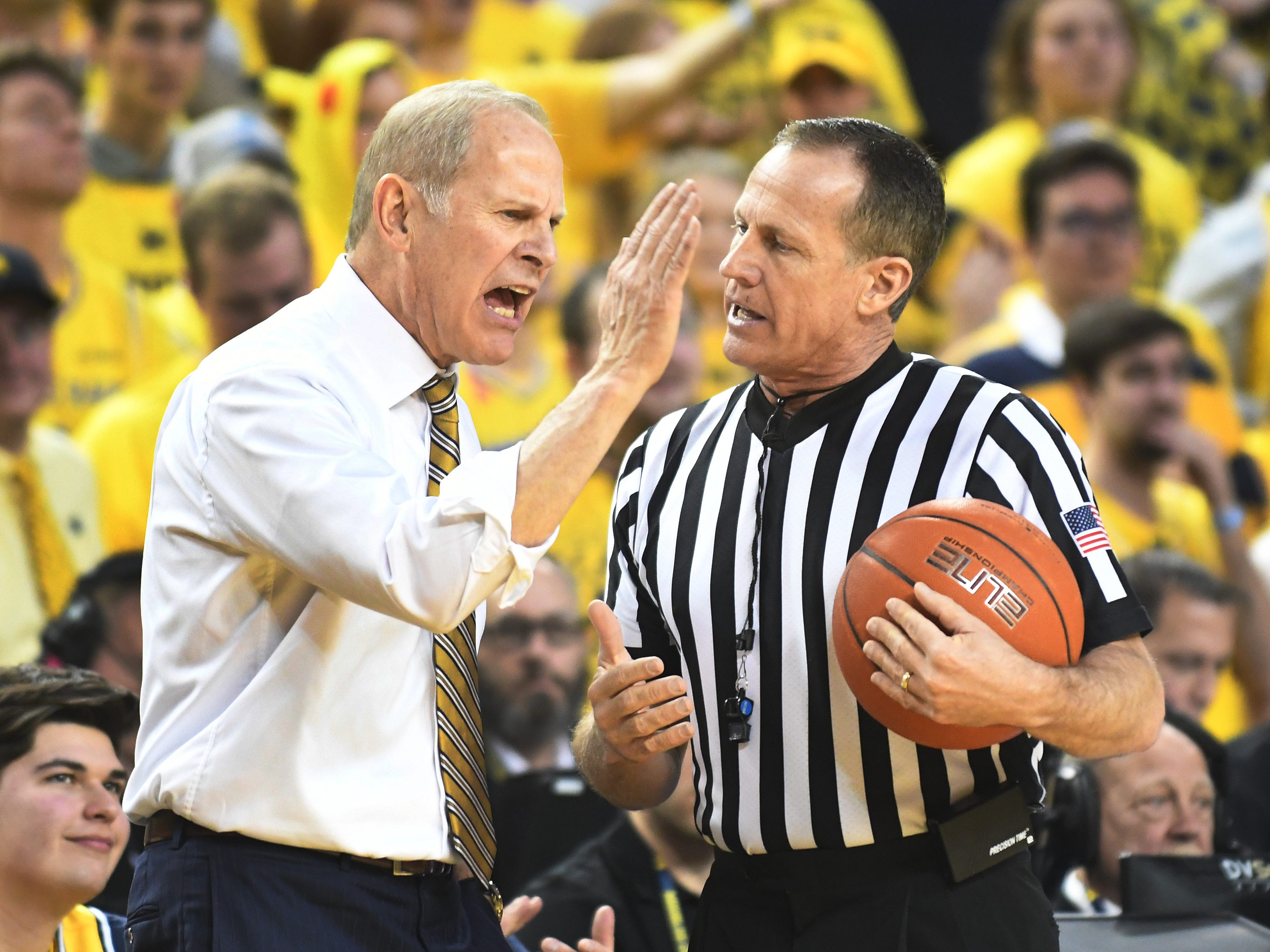 Michigan coach John Beilein has a disagreement with the ref during a break in the action in the first half.