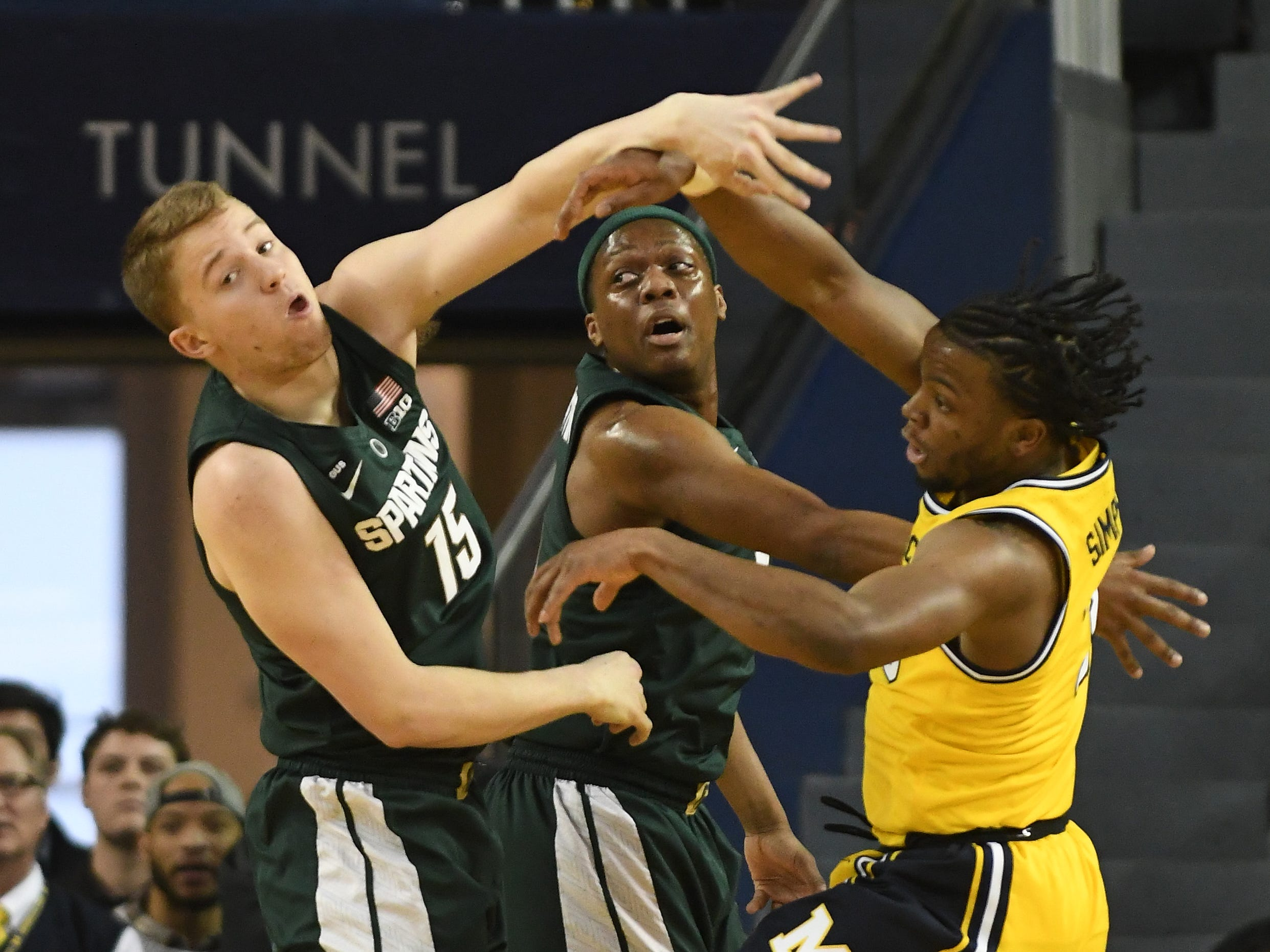 Michigan State's Thomas Kithier and Cassius Winston battle under the basket with Michigan's Zavier Simpson in the first half.