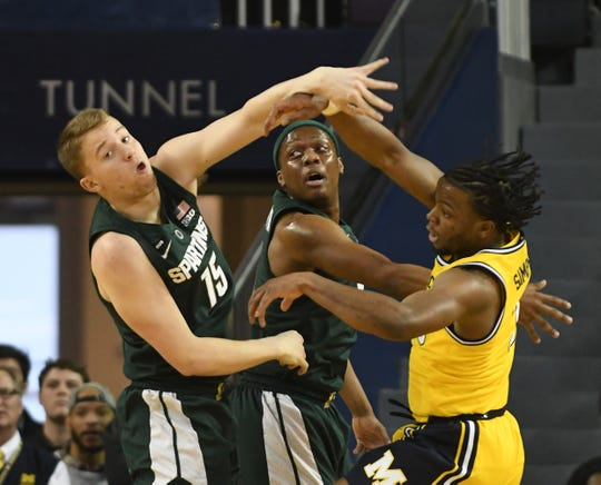 Michigan State's Thomas Kithier and Cassius Winston battle under the basket with Michigan's Zavier Simpson in the first half of the Spartans' victory over their rival last weekend.