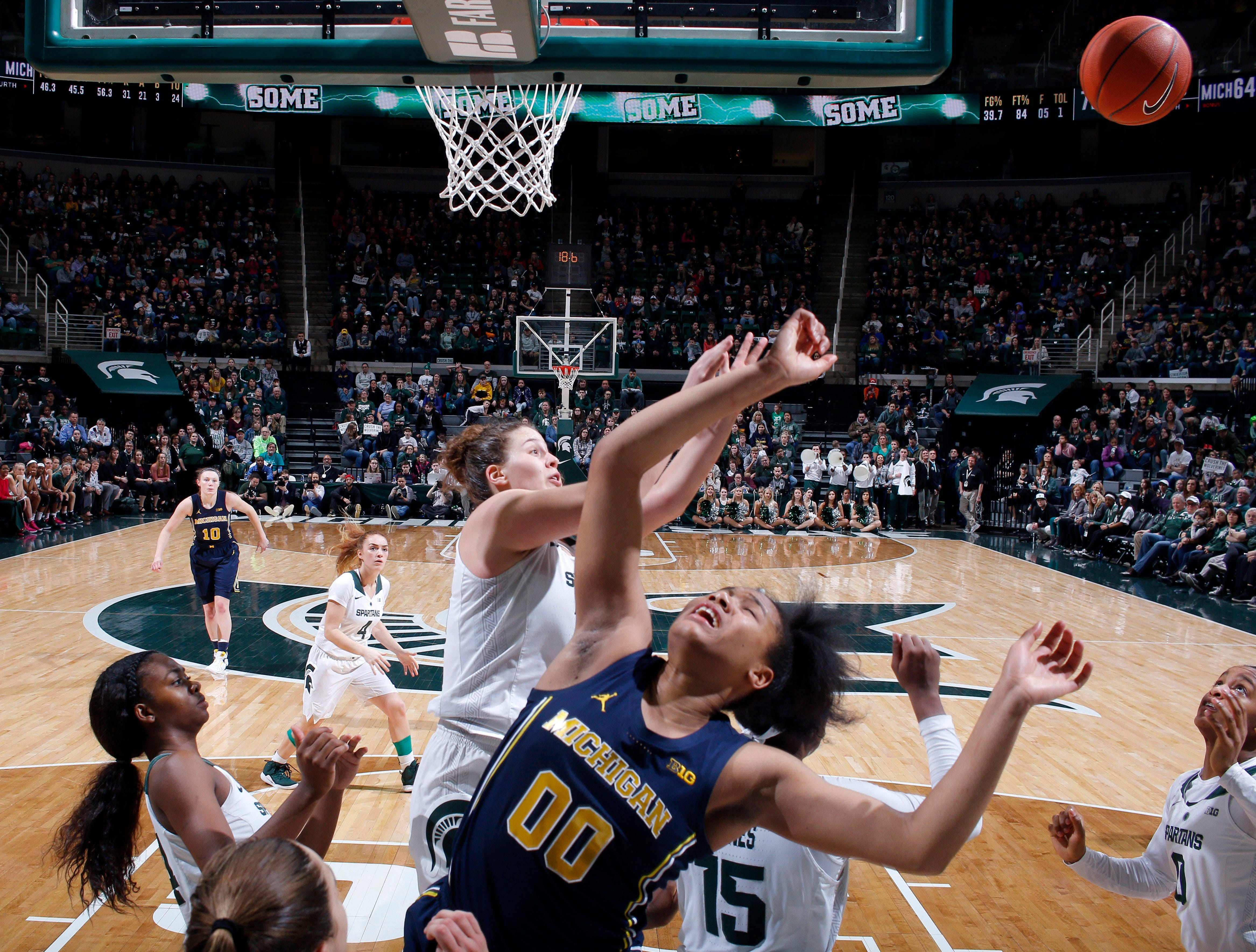 Michigan's Naz Hillmon (00) and Michigan State's Jenna Allen, center, battle for a rebound during the fourth quarter.