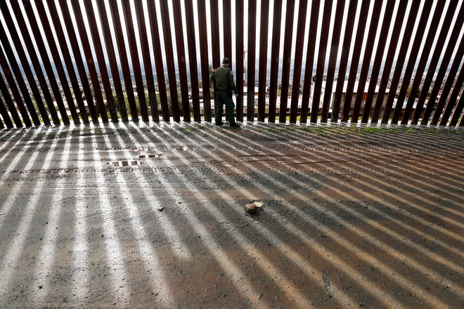 Border Patrol agent Vincent Pirro touches a section of the border wall separating Tijuana, Mexico, behind, from San Diego, Tuesday, Feb. 5, 2019, in San Diego. The House is expected to vote Tuesday to terminate President Trump's emergency declaration to build the border wall.