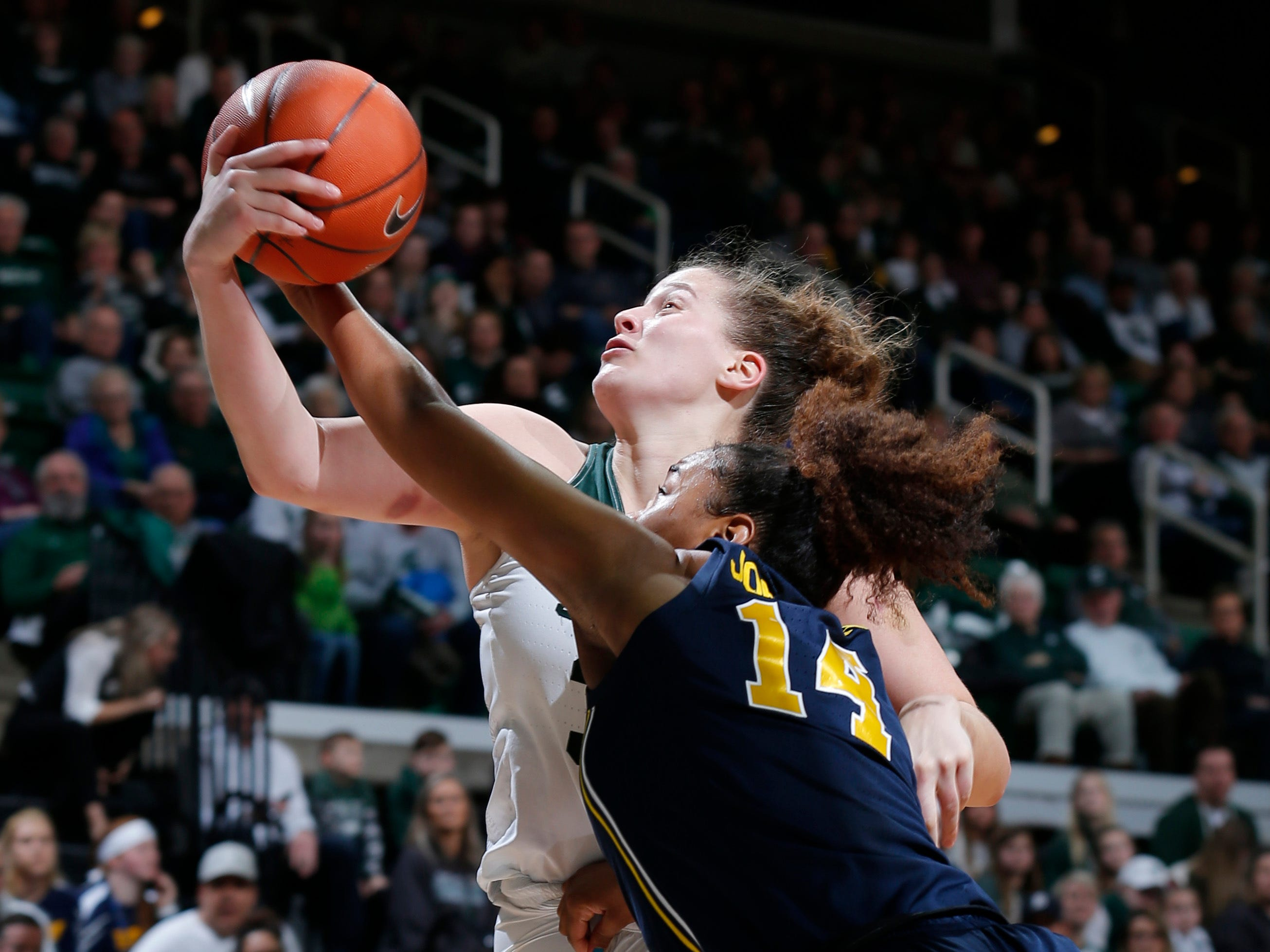 Michigan State's Jenna Allen, rear, and Michigan's Akienreh Johnson (14) vie for a rebound during the fourth quarter.