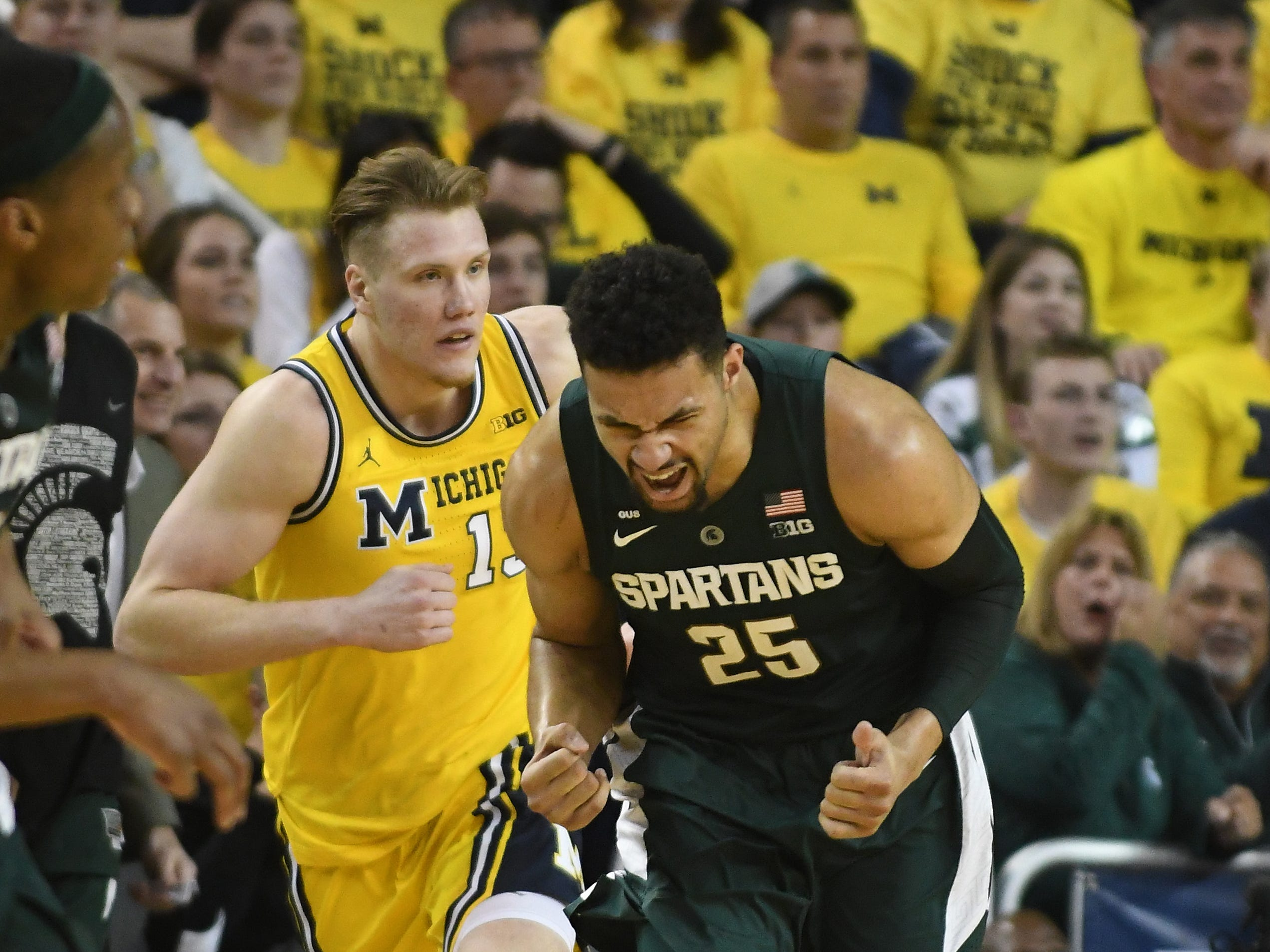 Michigan Kenny Goins reacts after a shot in front of State's Michigan's Ignas Brazdeikisin the second half.