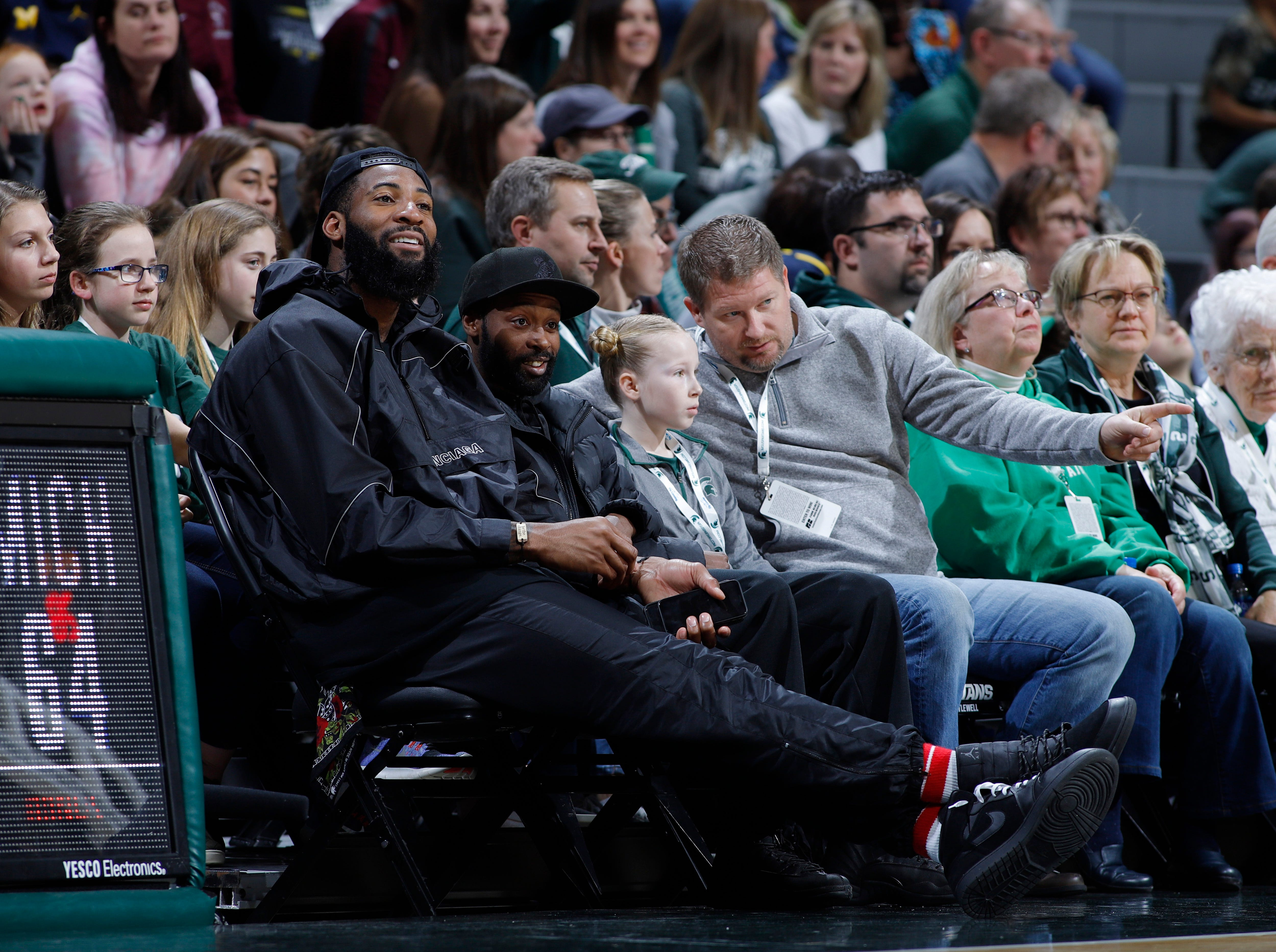 Detroit Pistons center Andre Drummond, left, watches the game from a courtside seat.
