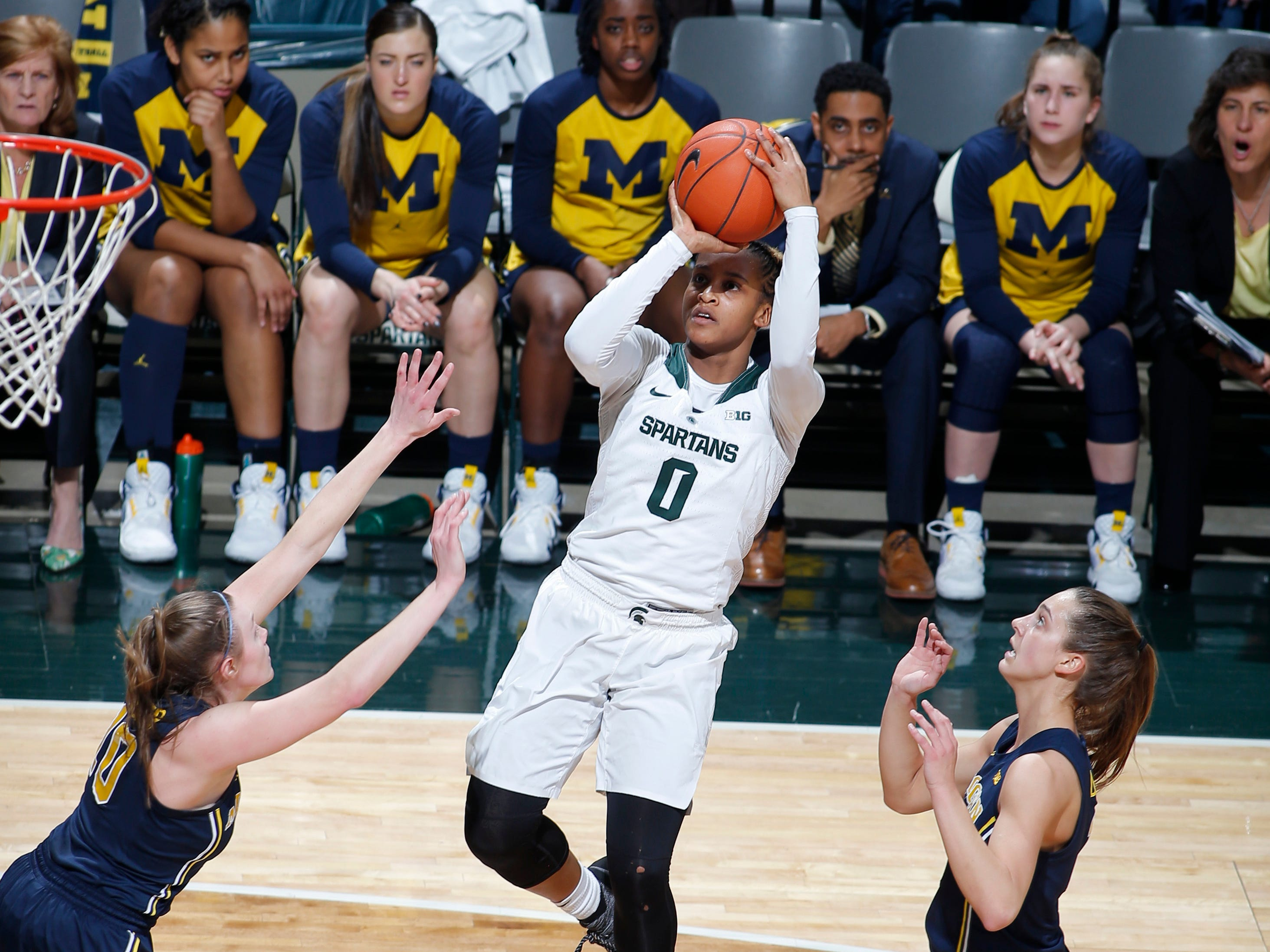 Michigan State's Shay Colley (0) shoots against Michigan's Nicole Munger, left, and Amy Dilk, right, during the second quarter.