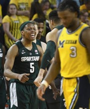 Michigan State's Cassius Winston celebrates as Michigan's Zavier Simpson walks off the floor after the MSU victory.