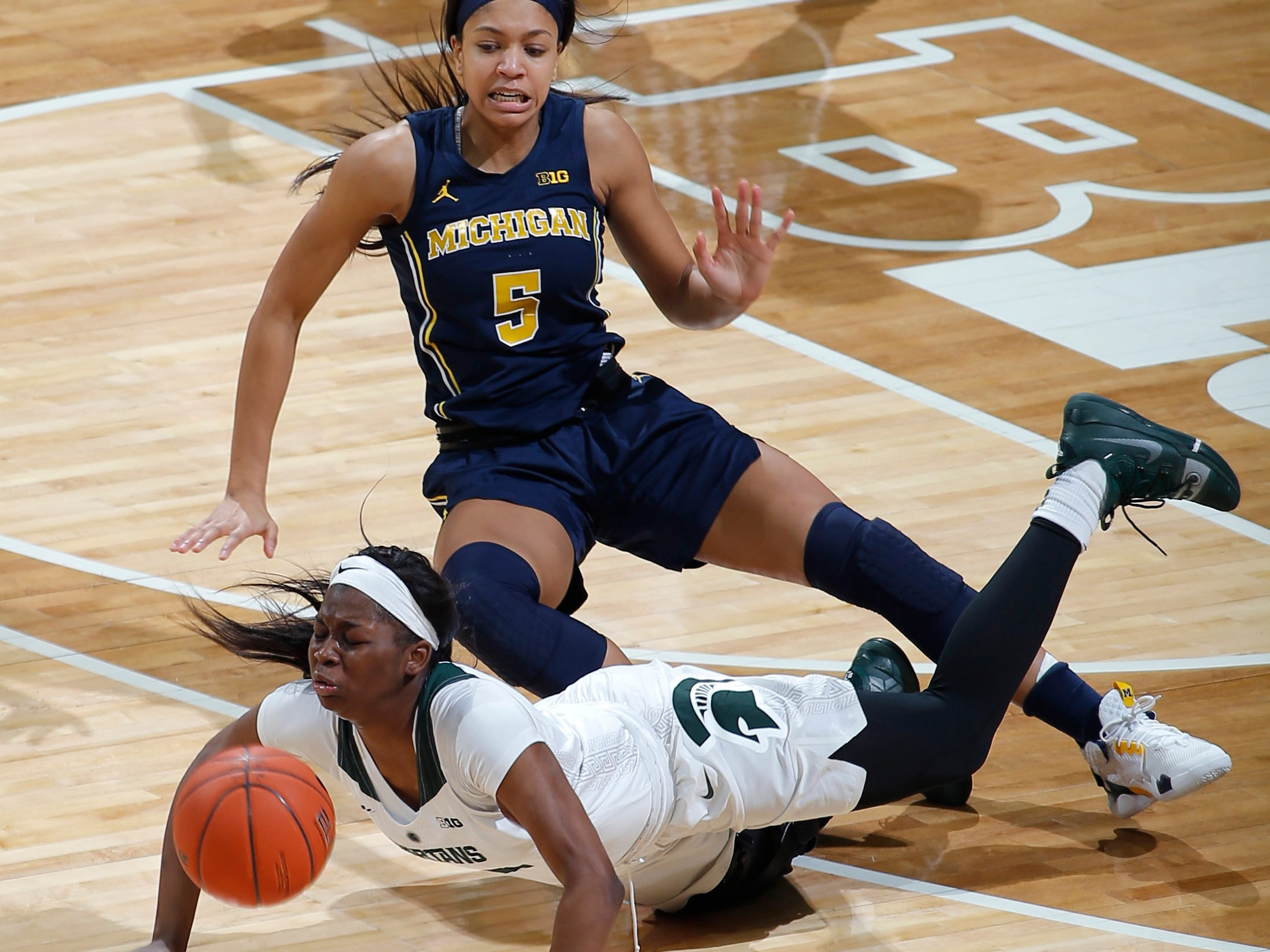 Michigan State's Mardrekia Cook, bottom, and Michigan's Kayla Robbins (5) collide during the second quarter.