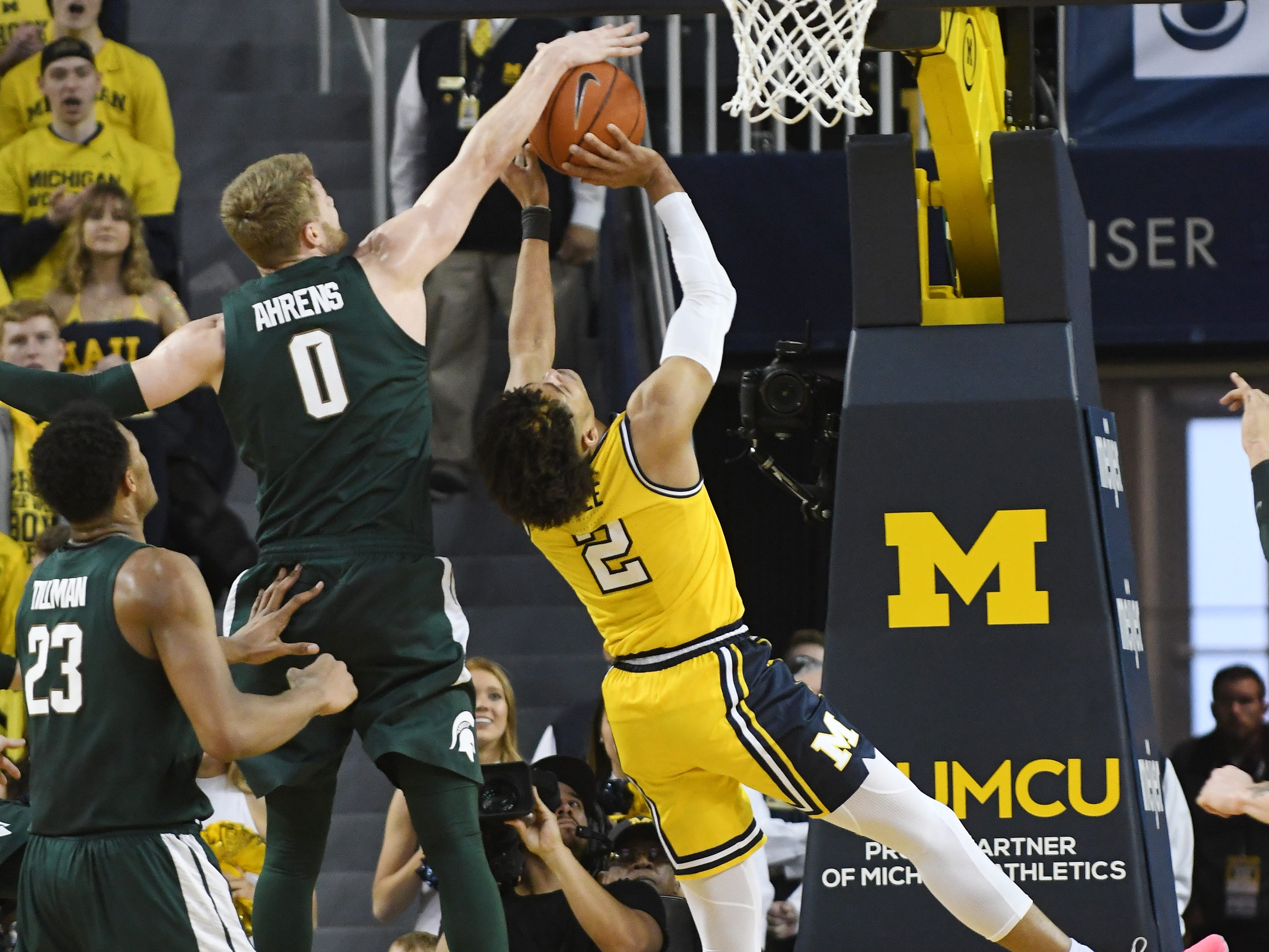 Michigan State's Kyle Ahrens blocks a shot by Michigan's Jordan Poole in the first half.
