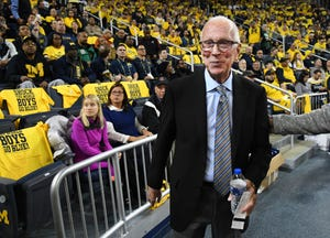 Former Michigan coach Steve Fisher heads to his seat for Sunday's game against Michigan State.