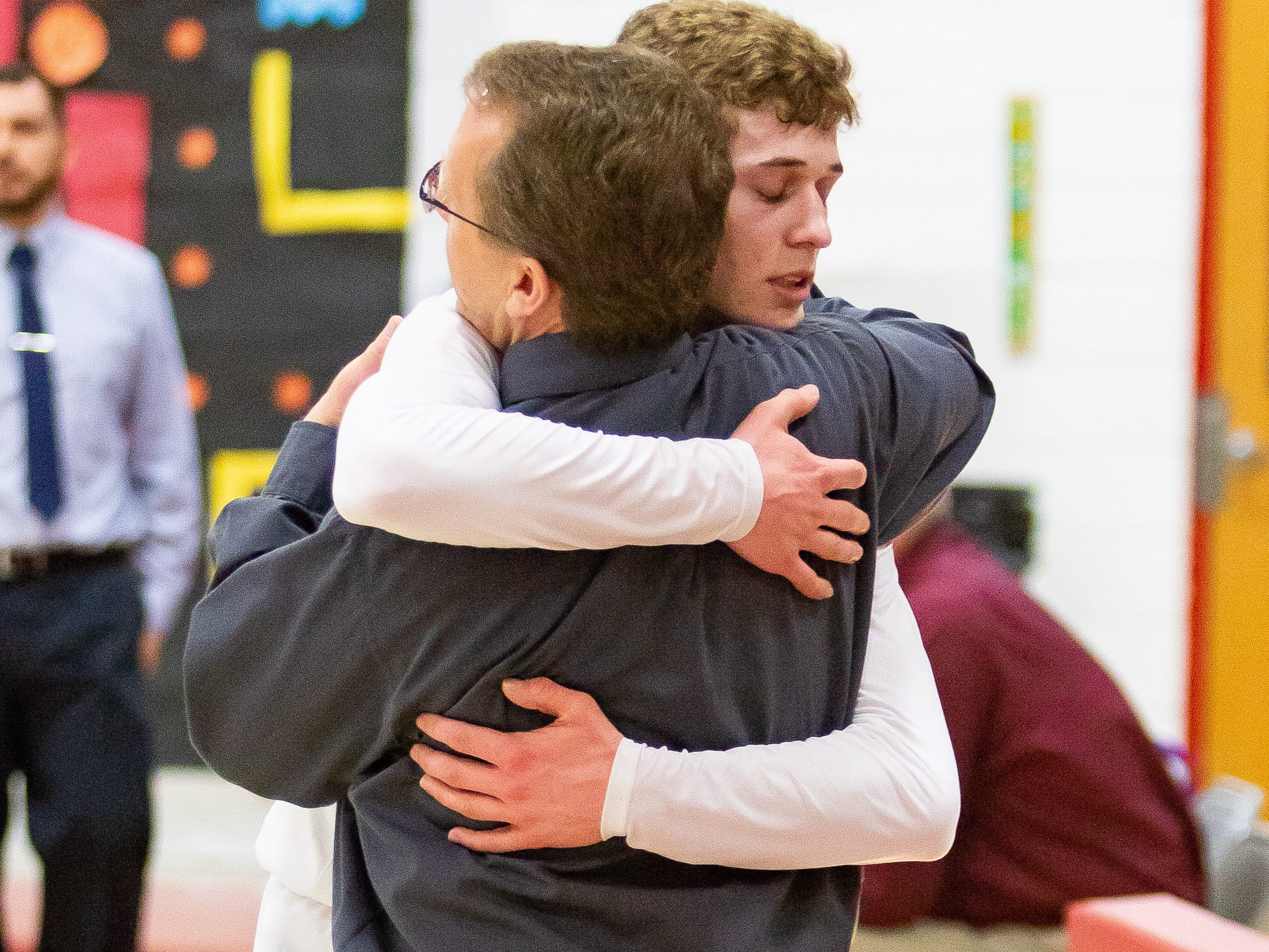 """Dylan Jergens hugs his dad and coach at Marcellus Howardsville Christian, Tim Jergens. """"It's a lot of fun, really a dream to have my dad coaching me and my brother playing with me."""""""