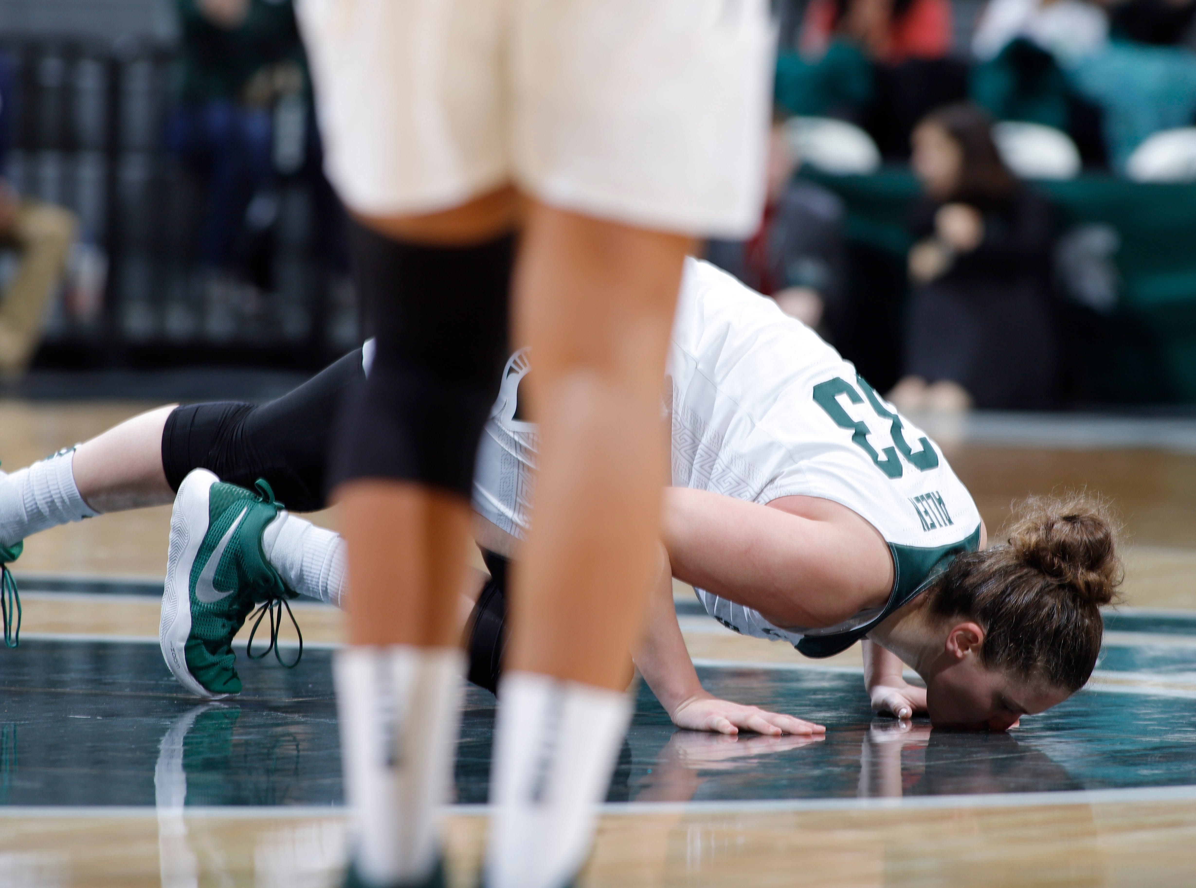 Michigan State senior Jenna Allen kisses the court in the final minutes of the game.